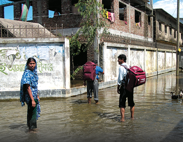 2 Men and 1 Women carrying Wagtech emergency kit backpacks in a flooded street