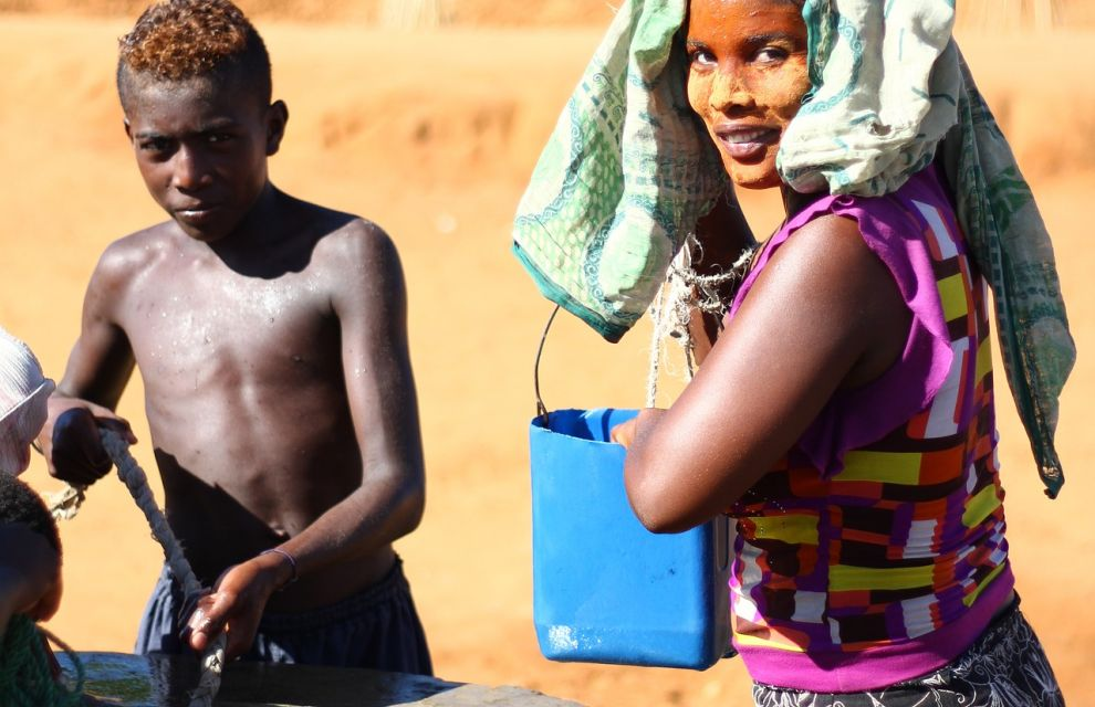 Women and boy filling a bucket with clean water from a tested well
